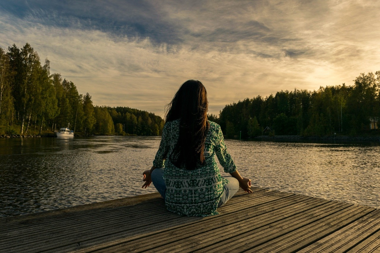 woman meditating near a lake- living life to fullest